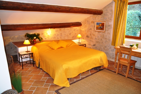 Mas des Oliviers at Moulin de la Roque, Noves, large Mastr bedroom, with cheerfull fabrics of Provence. Stunning view on the Oliva garden